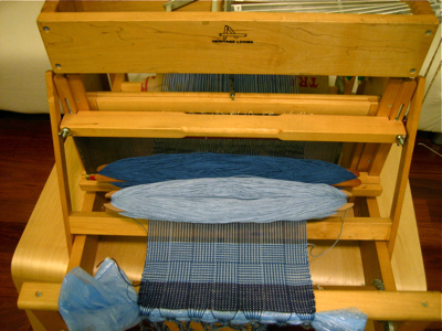 light blue and dark blue check log cabin design on the loom